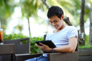 young asian man smiling while looking at a website on a tablet