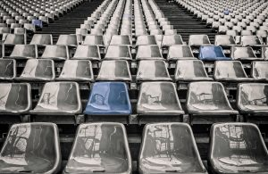 Rows of audience stadium seats with two seats a different color blue