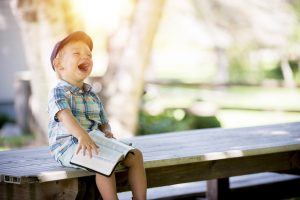 Little boy wearing a cap and sitting on a bench outside with sun shining while holding an open book and throwing his head back laughing