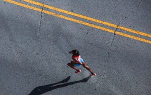 Aerial view of woman in running gear running down a blacktop road with a double yellow stripe