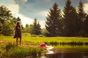Girls fishing with lines out into water on a sunny day