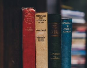 four older hard cover books standing on their ends in different colors