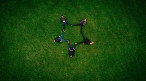 5 people laying on the grass with legs out to form a star with their bodies