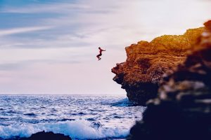 person jumping off of tall cliff into ocean