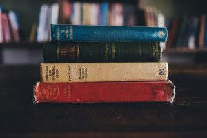 stack of colorful old books by famous authors