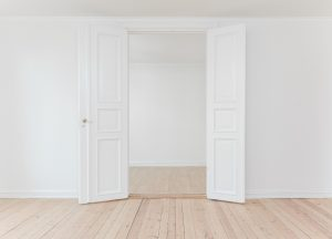 white double door with white walls open into a white room with hardwood floors