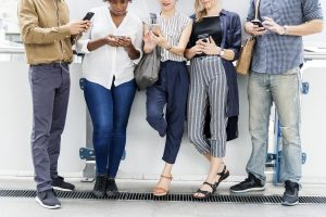 group of people standing against a wall looking down at cell phones