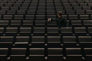 Man sitting in stadium alone looking around