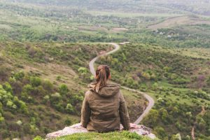 woman sitting on top of green hill looking out at road below