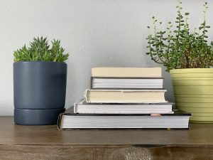 5 books stacked on a table with green plants next to them