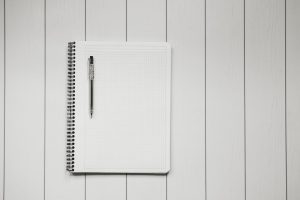 blank white notebook on blank white table with black pen