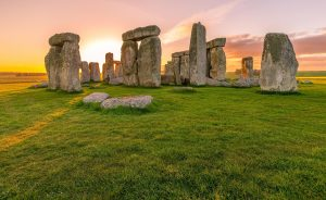 Stonehenge with sun setting in background.