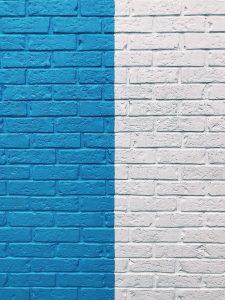 Brick wall half white and half bright blue