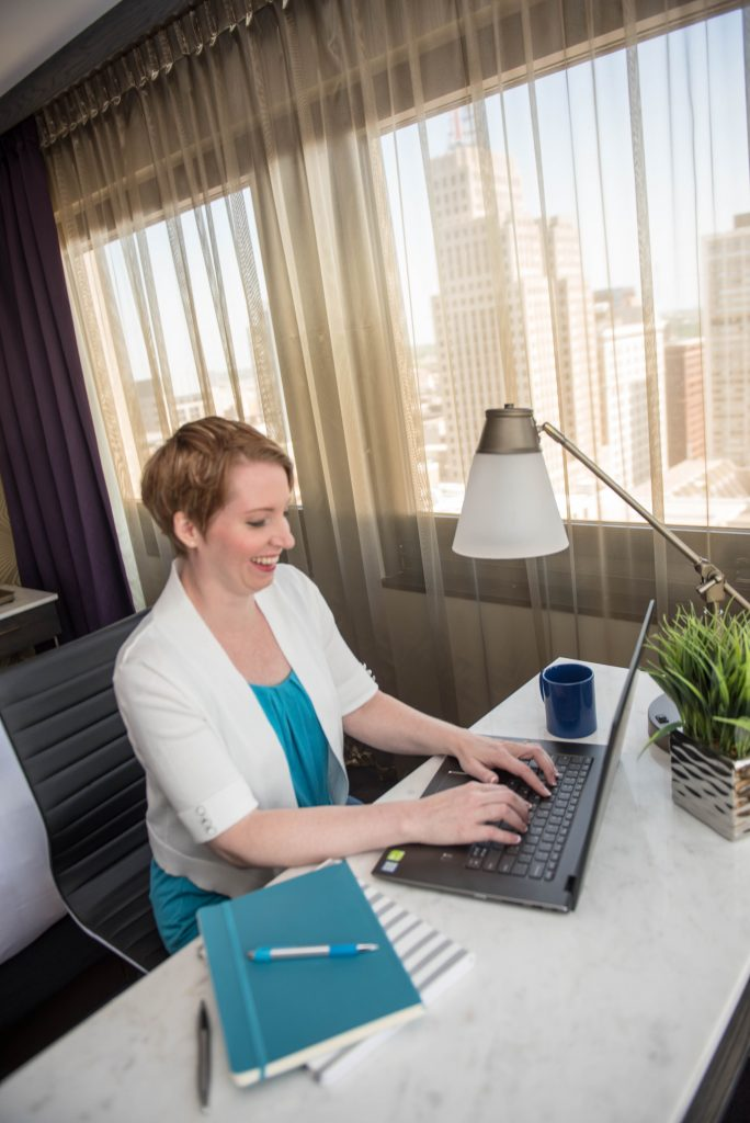 CCS Founder Cari Twitchell sitting at desk typing on laptop