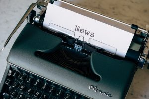 typewriter with paper displaying the word news