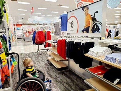 A little boy in a wheelchair looks at a Target ad featuring another boy in a wheelchair