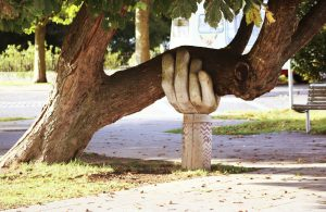 large carved hand holding up tree