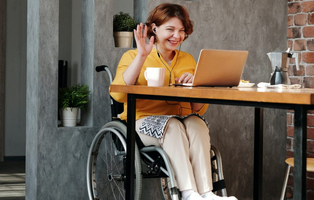 businesswoman in wheelchair at table with laptop