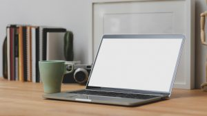 Blank laptop screen on desk with coffee cup