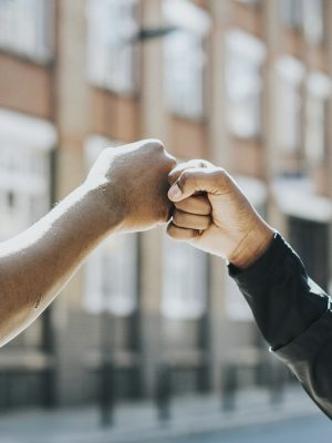 Arms reaching out and two hands meeting in a fist bump action