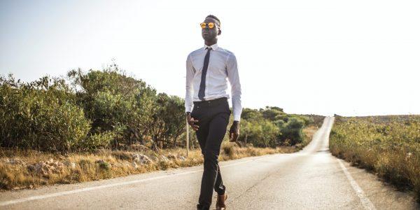 black man in suit walking on an empty road